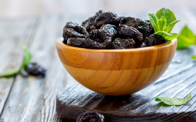 Dried black plums in bowl on wooden table, selective focus.